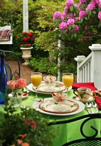 A bistro table with a bright green table cloth is set for breakfast for two