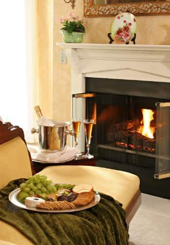 The cozy fireplace in a room with a setup of champagne and cheese & crackers nearby.