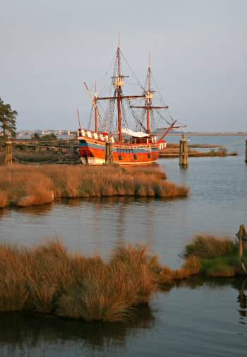 A red sailboat is docked near the shore with its sails drawn
