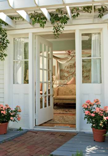 A beautiful white pergula covers a welcoming open door and  two pots of pink roses