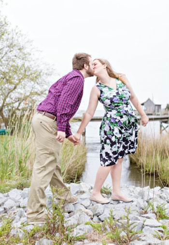 A man in a purple shirt leans in for a kiss from his bride while standing on the rocky shore