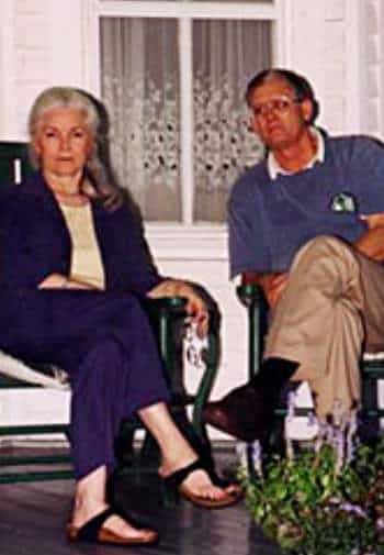 A woman in a purple suit and a man in a purple shirt sit together on the porch