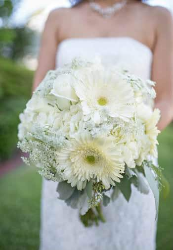 A  bride holds out her elegant bouquet of white and cream flowers