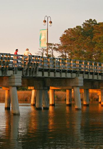 Two people enjoy the view of the river from a bridge , orange of the sunset makes the sky glow