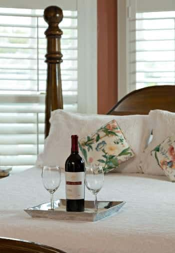 A silver tray with a bottle of wine and two wine glasses sits on the well made pink and whitebed