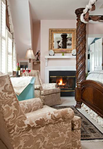 A pink cozy guestroom two gold arm chairs line the wall , fireplace roaring in thebackground