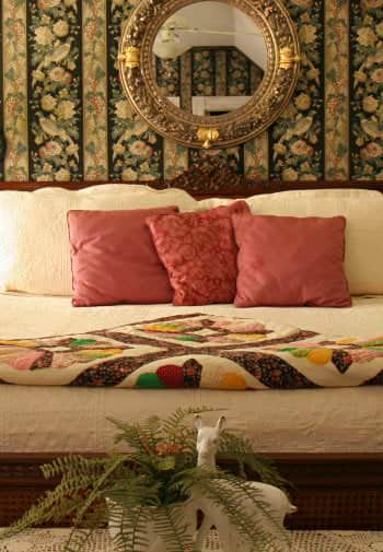 A cream colored king sized bed with red pillows and a multicolored quilt as accents
