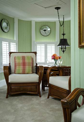 A cozy green and white guestroom is a sitting area are arm chairs with white cushions