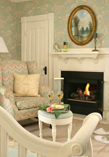Light green, pink and white guestroom with comfortable chairs around a cozy fireplace
