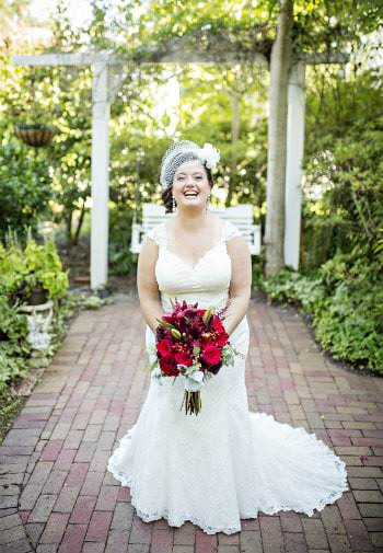 In a garden a smiling brides stands crouched ready to throw her beauitful red bouquet