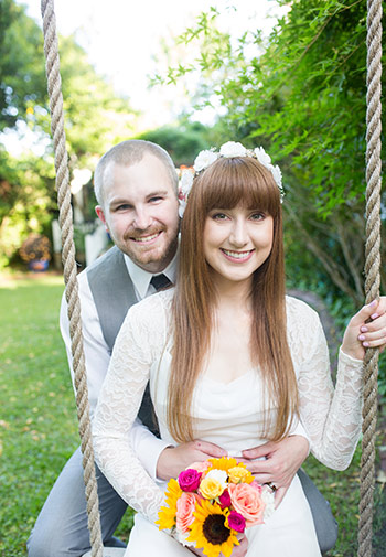 Smiling couple on swing, in grey suit and white wedding dress